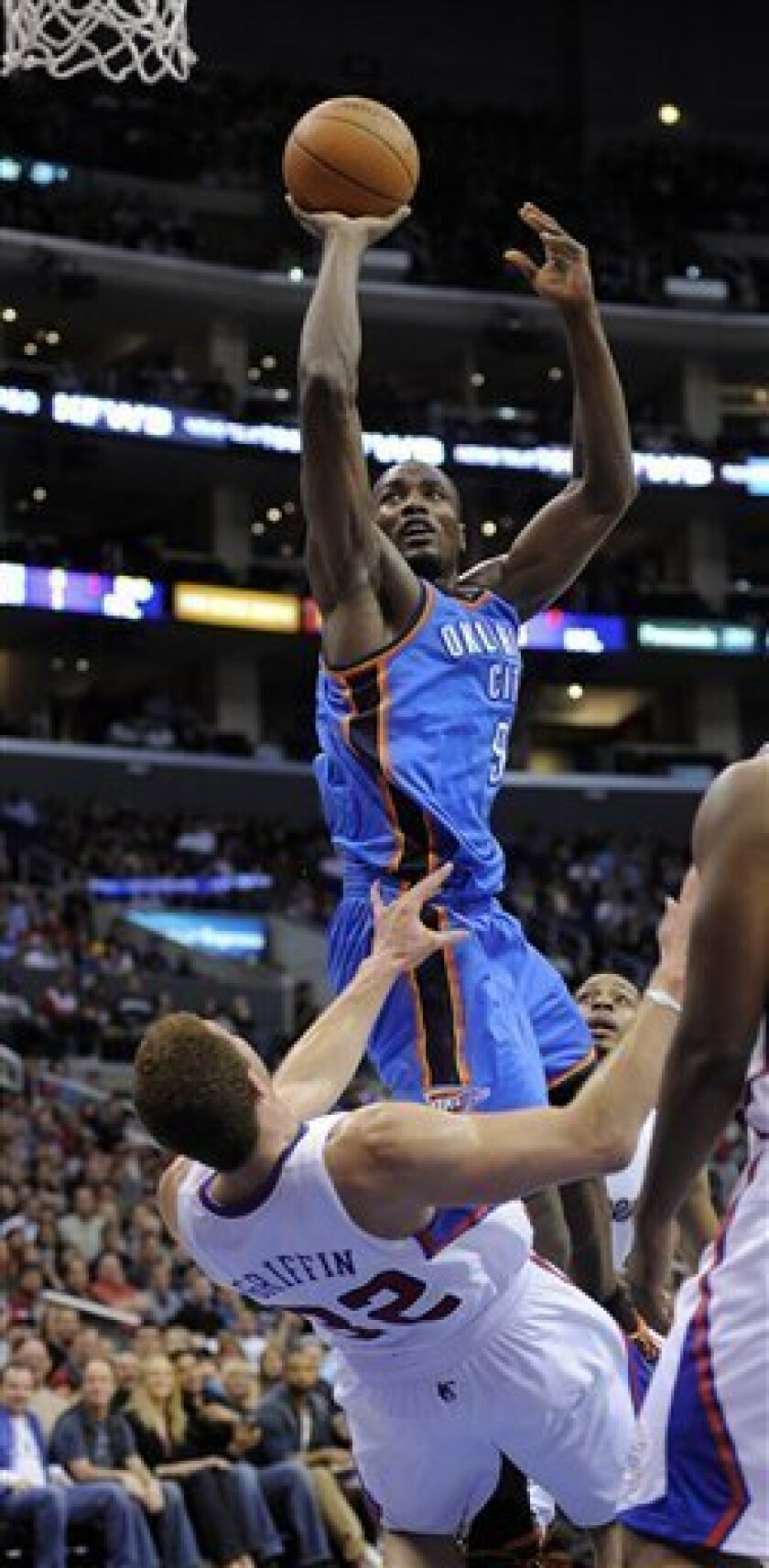 Oklahoma City Thunder forward Serge Ibaka, top, of the Republic of the Congo puts up as shot as Los Angeles Clippers forward Blake Griffin falls during the first half of their NBA basketball game on Saturday, April 2, 2011, in Los Angeles. (AP Photo/Mark J. Terrill)