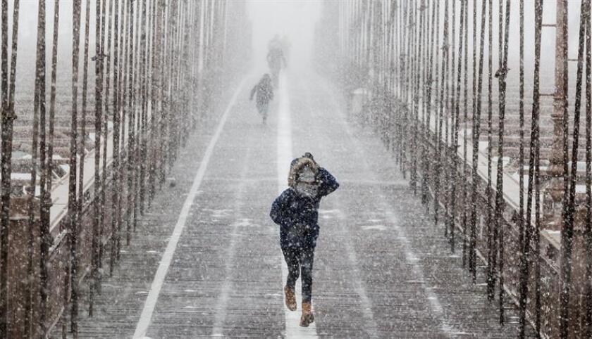 Peatones se protegen de la nieve y del viento mientras cruzan el puente de Brooklyn durante una tormenta de viento y nieve en Nueva York (Estados Unidos), hoy 4 de enero de 2017. EFE