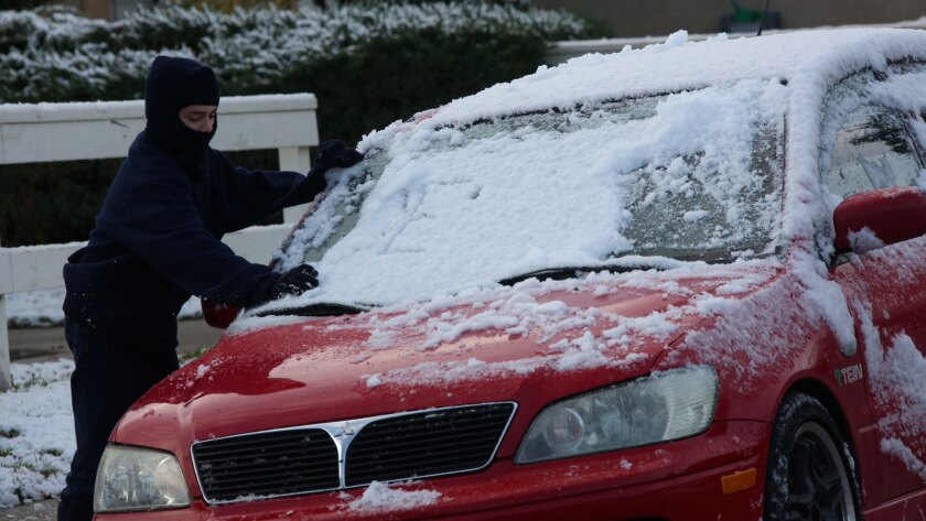 Bryant Forsythe, 11, clears snow off a car in Lake Elsinore amid the Dec. 31 Southern California deep freeze.