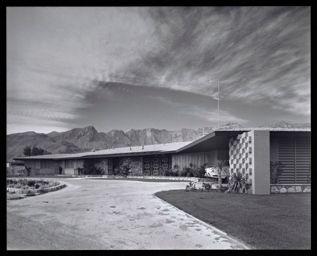 A black-and-white photo shows a low-slung Modern home with the San Jacinto Mountains in the distance.