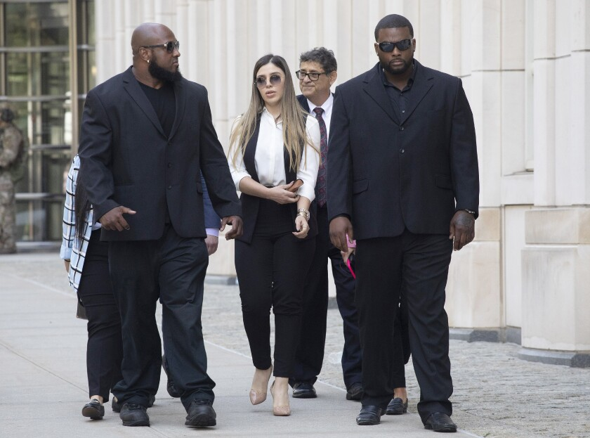"FILE- In this July 17, 2019 file photo, New York City police officer Ishmael Bailey, right, moonlights as a bodyguard for Emma Coronel Aispuro, wife of Mexican drug lord Joaquin ""El Chapo"" Guzman, as they leave Brooklyn federal court in New York, following Guzman's sentencing. Bailey was arrested on Wednesday, Sept. 18, 2019 on charges including possession and sale of a controlled substance, receiving bribes and official misconduct. Prosecutors say he transported cocaine for an undercover officer posing as a drug dealer. (AP Photo/Mark Lennihan, File)"