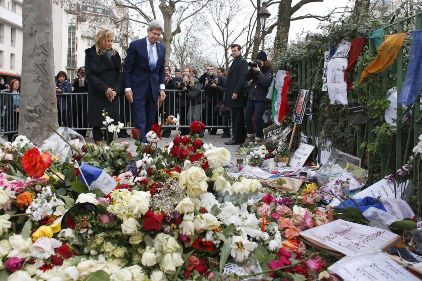 U.S. Secretary of State John F. Kerry and U.S. Ambassador Jane D. Hartley pay tribute to a police officer killed in the Charlie Hebdo attack at a memorial outside the magazine's offices in Paris on Jan. 16.