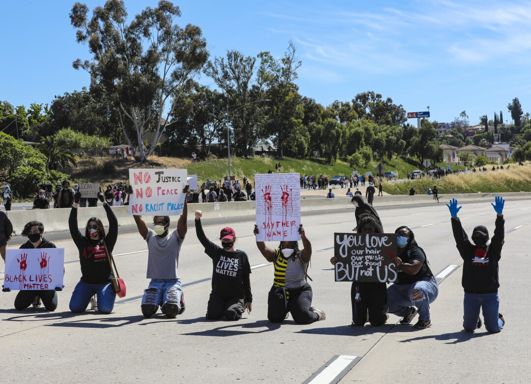 Protestors in support of calling for justice for George Floyd temporary blocked the westbound freeway lanes on Interstate 8 during a protest in La Mesa on Saturday.