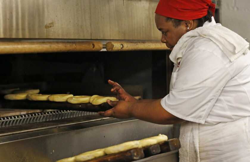 Sharelle Robbins tests a bagel before sliding it back in the oven atop a burlap-covered wooden plank, Thursday, May 26, 2016, at Kossar's Bagels and Bialys in New York. David Zablocki, one of the shop's owners and a classically-trained french chef, says the wood helps the bagels achieve a crispy bo