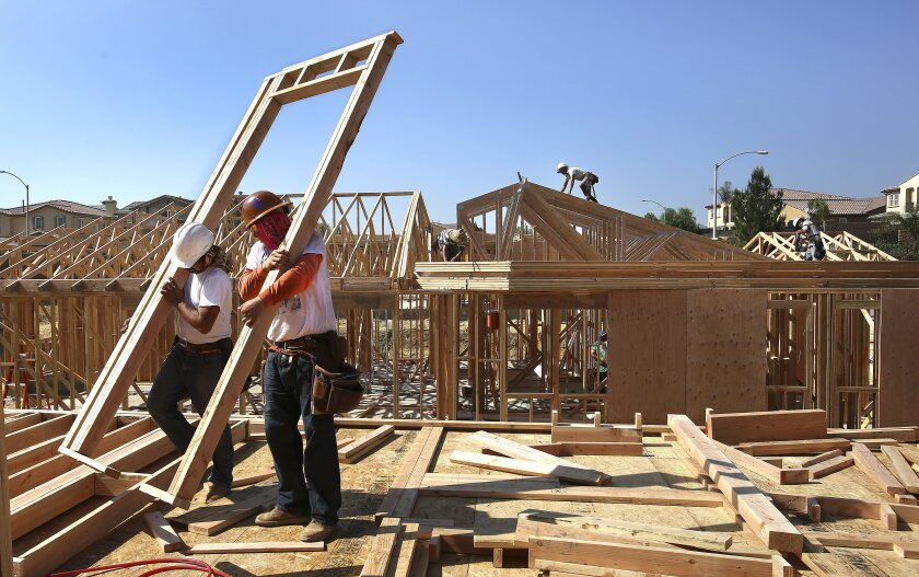 Workers in hardhats lift a a wooden frame at a construction site.
