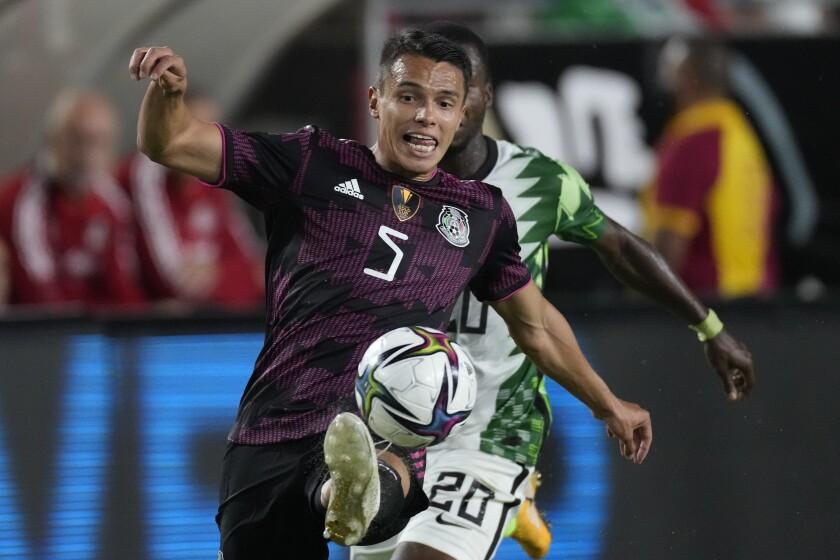 El defensor mexicano Oswaldo Rodríguez controla el balón frente al defensor nigeriano Emmanuel Olusi en la primera mitad.