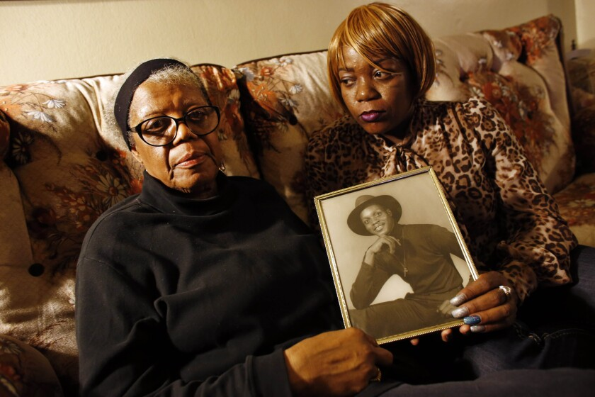 Alma Murdough, left, and her daughter Cheryl Warner hold a photo of Murdough's son, Jerome. On Feb. 15, jail staff discovered a lifeless Murdough in a 101 degree jail cell.