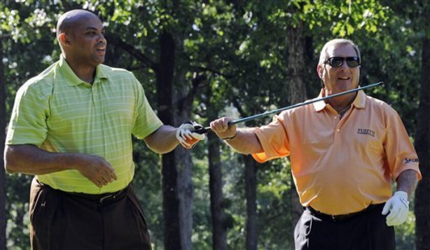 Former NBA basketball player Charles Barkley, left, and golfer Fuzzy Zoeller have fun after Barkley destroyed his driver on the first tee during the pro-am for the Regions Tradition Champions Tour golf tournament, Wednesday, May 4, 2011 in Birmingham, Ala.  (AP Photo/The Birmingham News, Bernard Tr