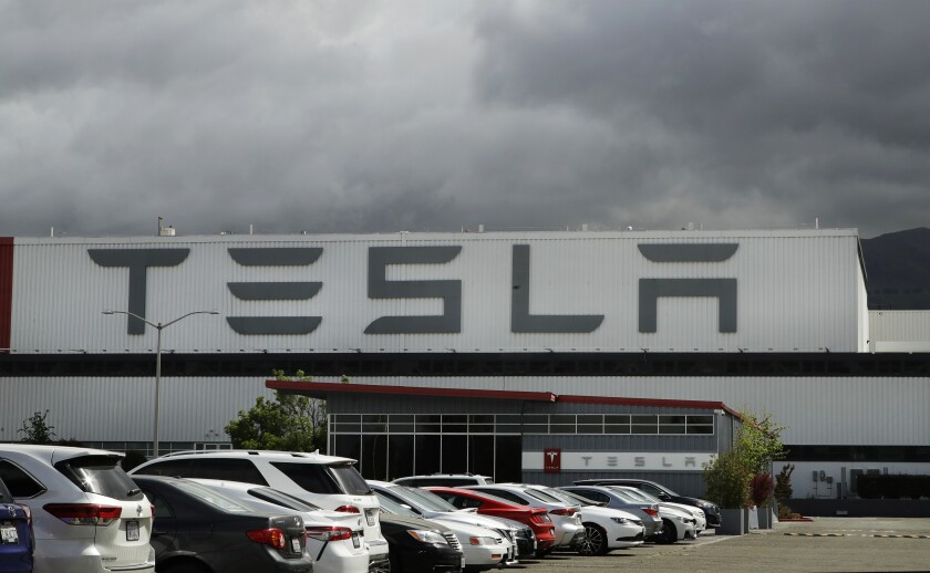 Employee cars are parked outside Tesla's plant in Fremont, Calif.