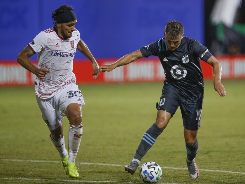 Real Salt Lake defender Marcelo Silva (30) and Minnesota United midfielder Robin Lod (17) battle for the ball during the first half of a soccer match in Kissimmee, Fla., Friday, July 17, 2020. (AP Photo/Reinhold Matay)