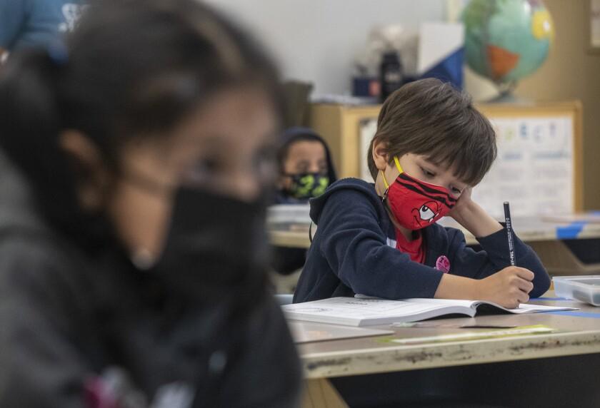 Alta California Elementary School kindergartner Louie Watkins writes in his math workbook
