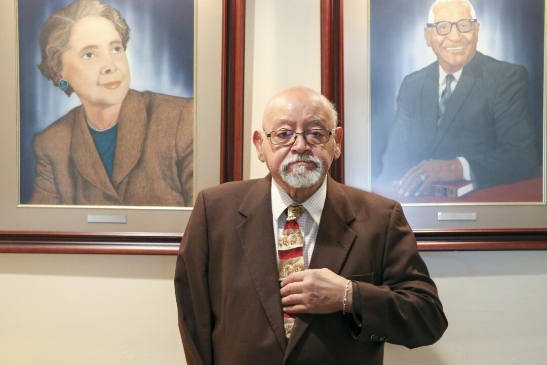 Jim Goodwin with paintings of his mother and father, Jeanne and E.L. Goodwin, in the lobby of the Oklahoma Eagle newspaper.