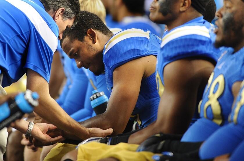 UCLA quarterback Brett Hundley has his left elbow checked out after suffering an injury in the first quarter.