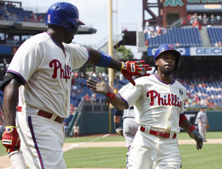 """FILE - In this Aug. 20, 2014, file photo, Philadelphia Phillies' Jimmy Rollins, right, celebrates his run with Ryan Howard on a single by Chase Utley during the fifth inning of the team's baseball game against the Seattle Mariners in Philadelphia. When Rollins made his first All-Star team as a rookie with the Phillies 20 years ago, the percentage of Black players in the majors was 13. It's down to 7.6% this year. Rollins pointed to Ken Griffey Jr. and Barry Bonds as popular players who were marketed well when he was growing up. """"But when you start going outside of that select few, the sport itself isn't marketing anyone else in a major way where kids from the inner cities are attracted to it,"""" he said. (AP Photo/Chris Szagola, File)"""