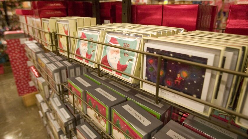Christmas and holiday cards are displayed on a rack for sale.