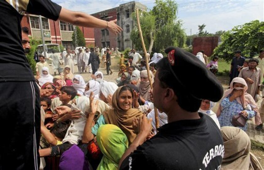 Pakistani flood-affected people argue with police officers demanding food relief at a camp set up in Nowshera in northwest Pakistan on Monday, Aug. 9, 2010. Pakistan will need billions of dollars to recover from its worst floods in history, further straining a country already dependent on foreign a