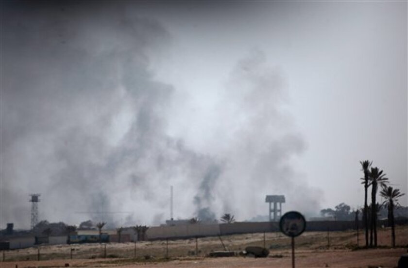 In this image taken from a bus heading to an organized trip by the Libyan authorities, smoke rises from a Libyan military base on the outskirt of Tajura, 30 kms (20 miles) east of Tripoli, Libya, Friday March 25, 2011. NATO agreed to take over command of the newly established no-fly zone over Libya, but the alliance's new role doesn't allow the U.S. to make a quick exit from the costly military operation as the Obama administration had wanted.(AP Photo/Jerome Delay)