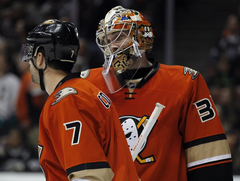 Ducks goalie John Gibson talks with center Andrew Cogliano, left, during a break in play against the Kings on Jan. 17.