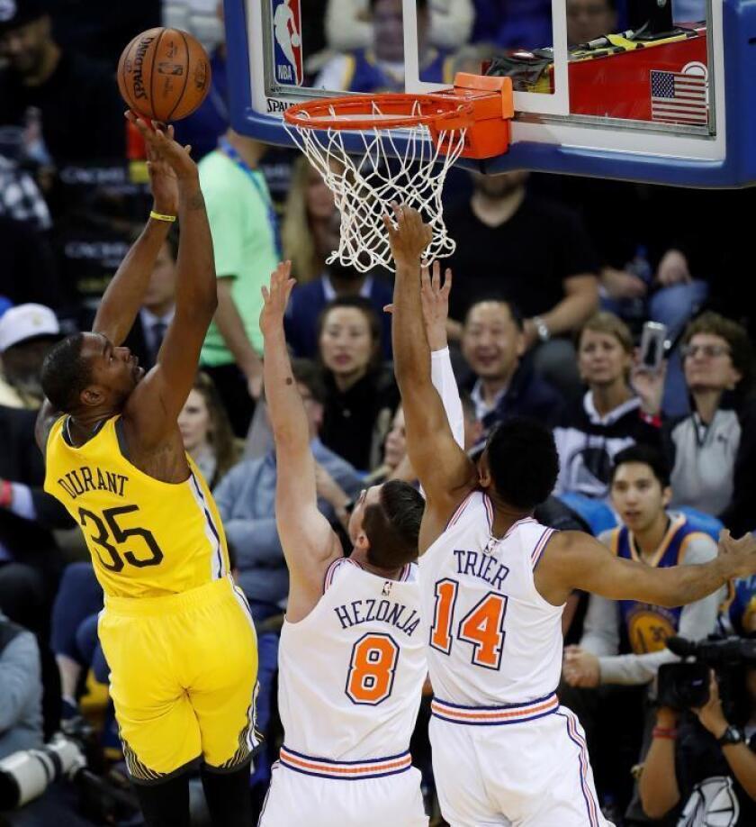 El alero de los Warriors de Golden State Kevin Durant (i) lucha por el balón con el alero de los Knicks de Nueva York Mario Hezonja (c) hoy, durante el partido de baloncesto de la NBA, entre los New York Knicks y los Golden State Warriors, en el Oracle Arena de Oakland, California (EE.UU.). EFE