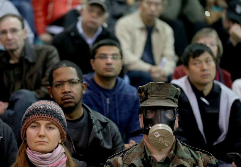 Brian Seligman, a former Marine, wears a gas mask as he joins hundreds of people gathered in the gym of Granada Hills Charter High School to participate in a meeting of the South Coast Air Quality Management District last week.