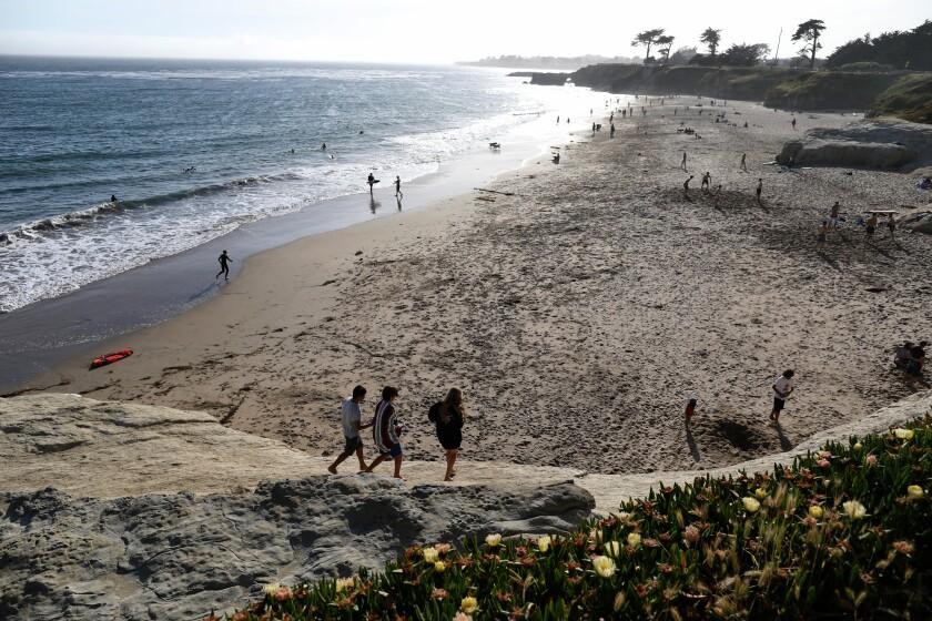Beachgoers trek across Lighthouse Field State Beach in Santa Cruz.
