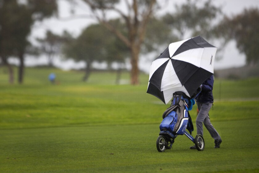 Linda Holmgren of Carmel Valley, using a umbrella to protect herself from the the rain, finishes the last of nine holes before drying out at the Torrey Pines Golf Course, Tuesday morning.
