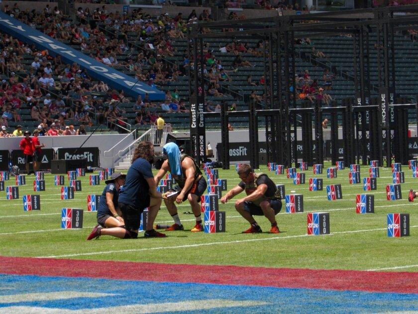 "San Diegan Dan Bailey, right, performs the last of 300 squats during ""Murph"" at the CrossFit Games."