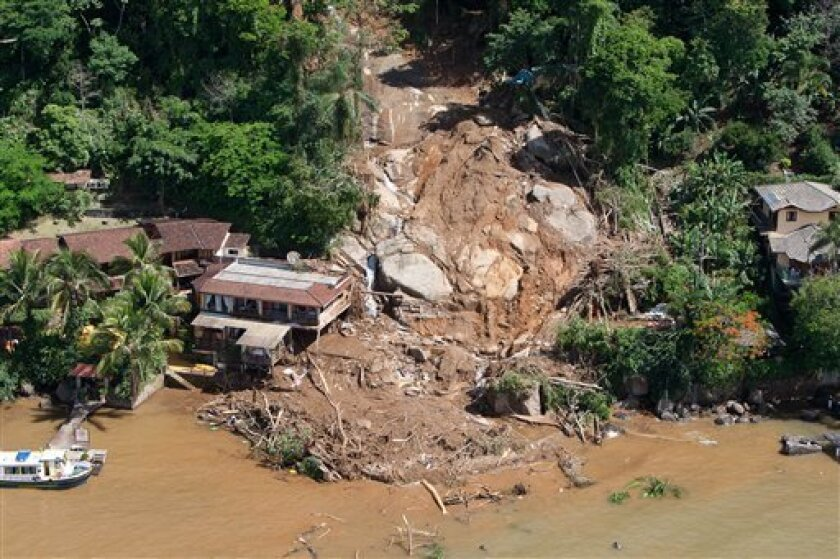 Earth covers homes in Ilha Grande, an island off the city of Angra dos Reis near Rio de Janeiro, Brazil, Friday, Jan. 1, 2010. A rain-soaked hillside collapsed on three houses and an upscale lodge after New Year celebrations, killing at least 15 people, according to Brazilian authorities. (AP Photo/Felipe Dana)