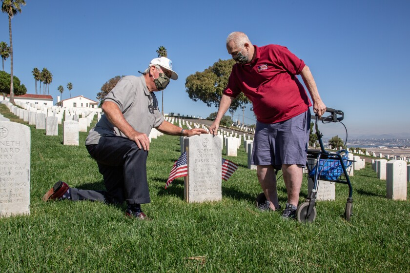 Vietnam veterans Dennis Schoville and Steven Brown visit the grave of Bobby Baker, who saved their lives in 1969.