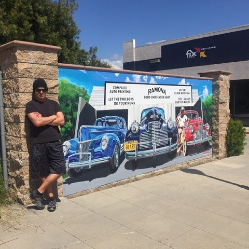 Artist David Hernandez next to his Ramona Body and Fender Shop mural, being dedicated Aug. 1.