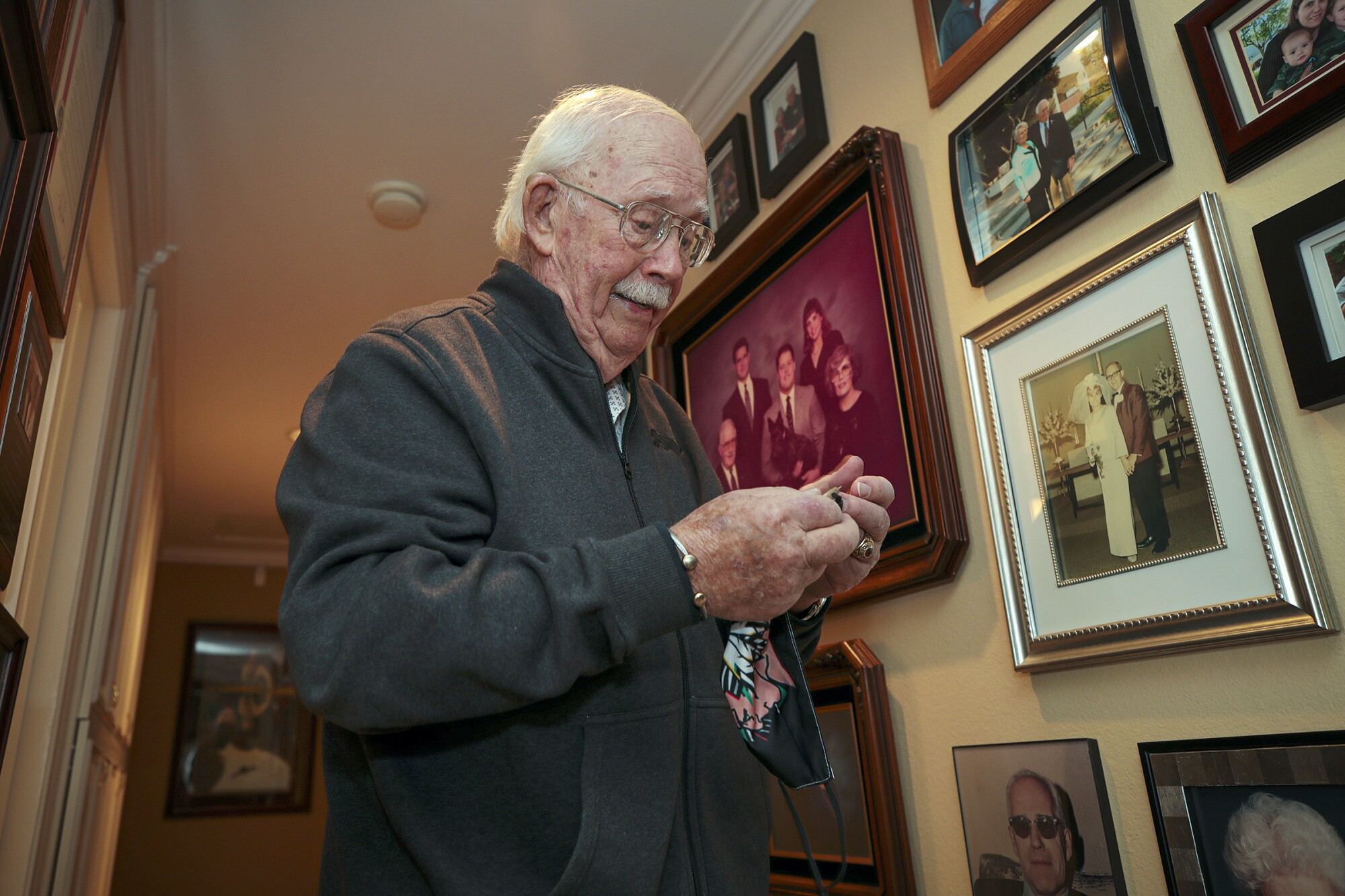 An elderly man looks at a handkerchief in his hands while standing next to a wall of family photos in his home