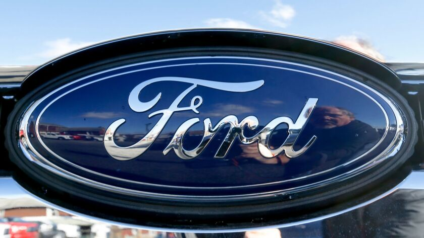 FILE - This Thursday, Nov. 19, 2015, file photo, shows the Ford badge in the grill of a pickup truck