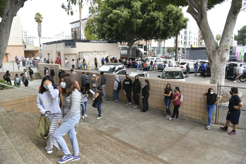 Students wait in line to pick up school resources at Hollywood High School.