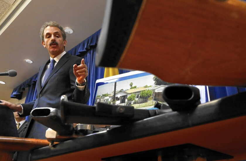 L.A. City Atty. Mike Feuer, at a news conference Tuesday, shows a table of weapons confiscated from a Watts home.
