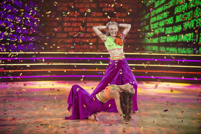 A blond woman in vibrant outfit poses behind a brunet woman in a matching outfit, surrounded by confetti