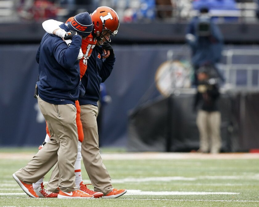 Illinois quarterback Wes Lunt (12) is helped off the field after being injured during the second half of an NCAA college football game against Purdue on Saturday, Oct. 4, 2014, in Champaign, Ill. (AP Photo/Andrew A. Nelles)