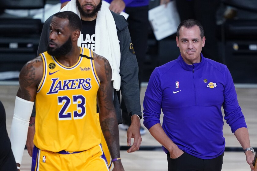 Lakers forward LeBron James, left, and coach Frank Vogel walk onto the court during a timeout.