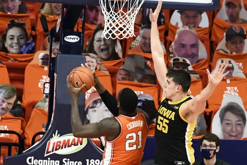 Iowa center Luka Garza (55) looks to block the shot of Illinois center Kofi Cockburn (21) in the first half of an NCAA college basketball game Friday, Jan. 29, 2021, in Champaign, Ill. (AP Photo/Holly Hart)