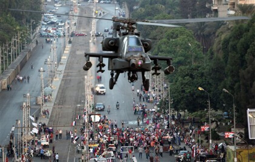 """A military attack helicopter flies near the presidential palace in Cairo, Egypt, Friday, July 5, 2013. The top leader of Egypt's Muslim Brotherhood has vowed to restore ousted President Mohammed Morsi to office, saying Egyptians will not accept """"military rule"""" for another day. General Guide Mohammed Badie, a revered figure among the Brotherhood's followers, spoke Friday before a crowd of tens of thousands of Morsi supporters in Cairo. A military helicopter circled low overhead. (AP Photo/Khalil"""