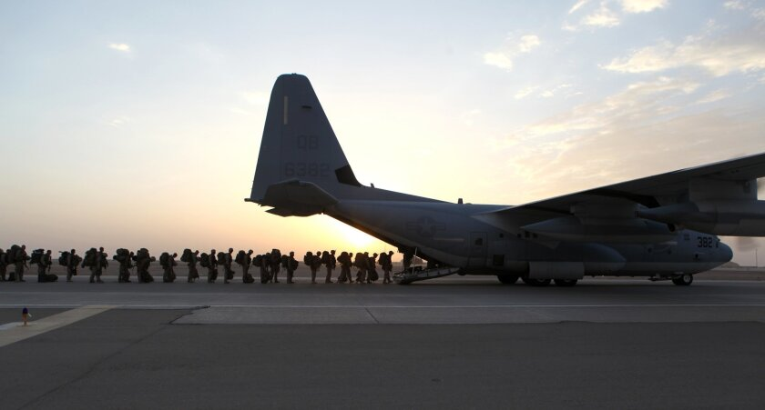 This handout photo provided Defense Department shows Marines and sailors with Marine Expeditionary Brigade – Afghanistan load onto a KC-130 aircraft on the Camp Bastion, Afghanistan flightline, Monday, Oct. 27, 2014. The handover of the U.S. Marines' main base to Afghan control in the hardscrabble