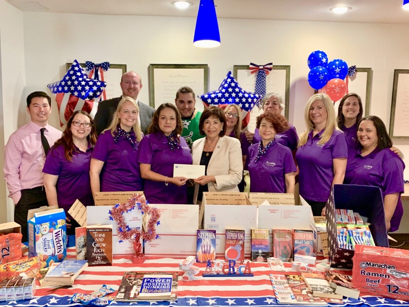 Chula Vista Mayor Mary Casillas Salas, in a white blazer, helps volunteers put together care packages for a group of Army soldiers deployed in the Middle East