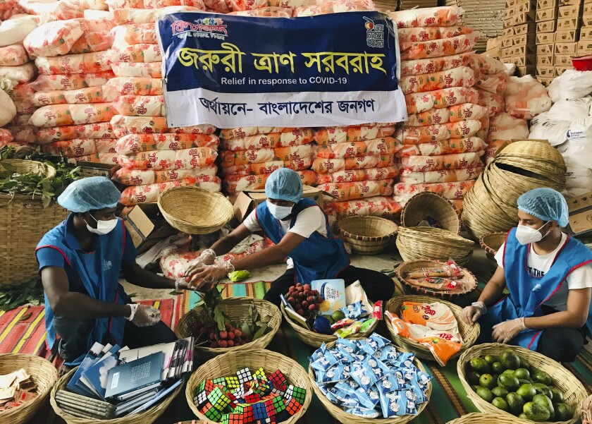"""Members of Bidyanondo Foundation pack care packages for COVID-19 patients in Dhaka, Bangladesh, Saturday, June 6, 2020. The Bangladeshi group of volunteers is providing COVID-19 patients with fruit baskets and """"get well soon"""" cards to keep their spirits up amid reports that many patients are being ostracized by their families and neighbors. The group stepped in after disturbing news reports that a woman has been abandoned in a forest by her family after she developed coronavirus symptoms. (AP Photo/Al-emrun Garjon)"""