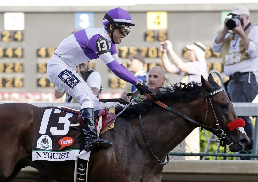 Mario Guitierrez celebrates after riding Nyquist to victory during the 142nd running of the Kentucky Derby.