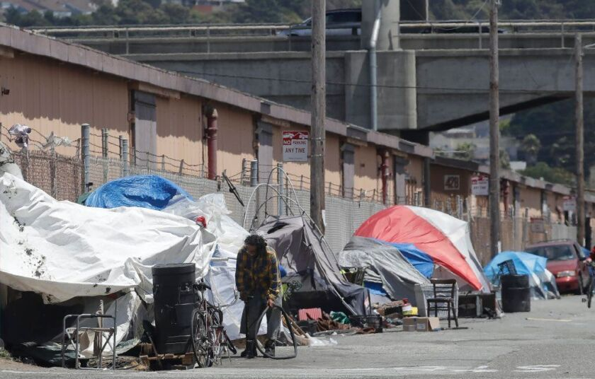 This June 27 photo shows a man holding a bicycle tire in a tent encampment along a street in San Francisco.