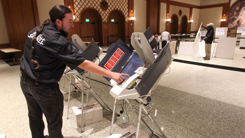 Touch screen trainer for the Registrar of Voters Israel Pelayo sets up touch screen voting machines for training as poll workers put together voting booths in the background as they prepare for Tuesday's vote at Montezuma Hall at SDSU.