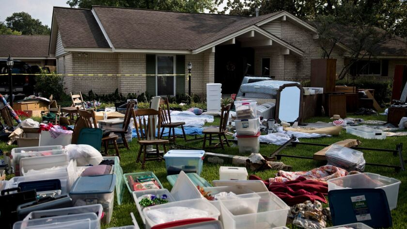 A family's possessions are spread out in the front yard for insurance adjusters as residents begin t