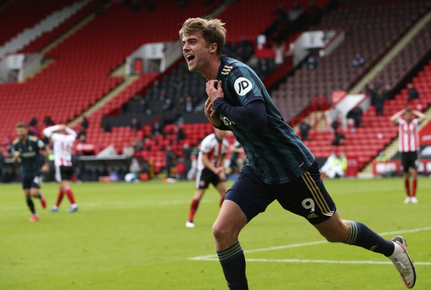 Leeds United's Patrick Bamford runs to celebrate after scoring his sides first goal during the English Premier League soccer match between Sheffield United and Leeds United at Bramall Lane stadium in Sheffield, England, Sunday, Sept. 27, 2020. (Alex Livesey/Pool via AP)
