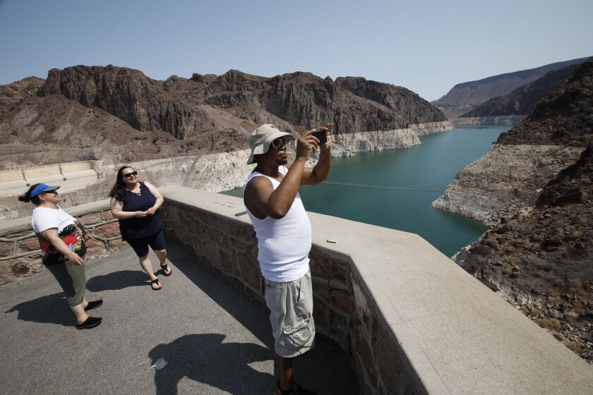 Eric Bonner of Lansing Mich. visits the Hoover Dam in the Arizona side with his mother-in-law Zina Ibragimova, left, and his sister-in-law Gamar Ibragimovai, center, Thursday, July 15, 2021. A coalition of activists, conservationists, elected officials, and business and agricultural interests gather at Hoover Dam to call for a moratorium on what they call wasteful uses of Colorado River water including dam and diversion projects. (Chitose Suzuki/Las Vegas Review-Journal via AP)
