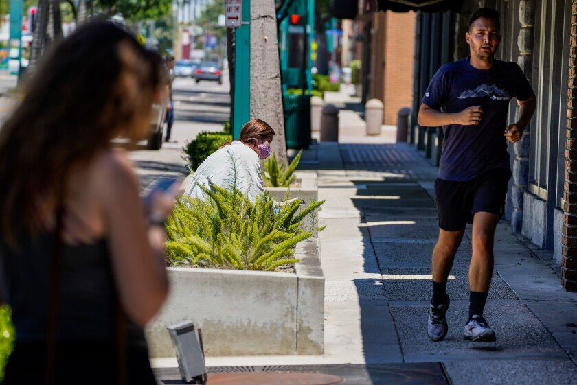 A man jogs along Harbor Boulevard in downtown Fullerton last week after Orange County rescinded its mask order.