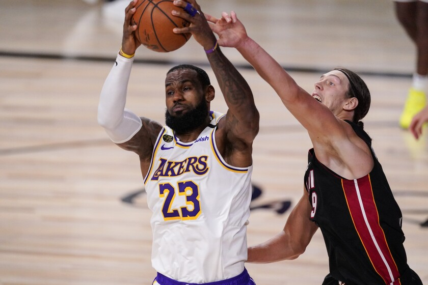 The Lakers' LeBron James and the Miami Heat's Kelly Olynyk fight for control for the ball.